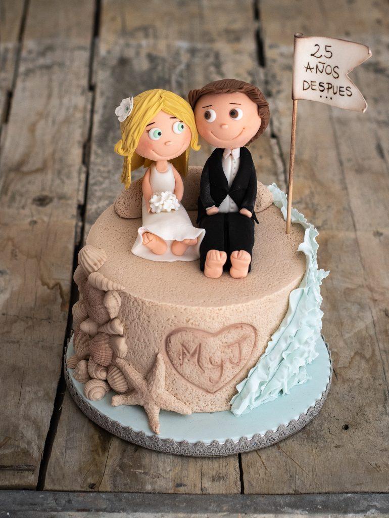tarta novios sentados en la arena con mar y conchas con cartel 25 años mas tarde by ponona cakes santander